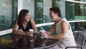 Two women sit laughing together at a coffee shop table outdoors, leaning forward on the table, each holding a disposable coffee cup.