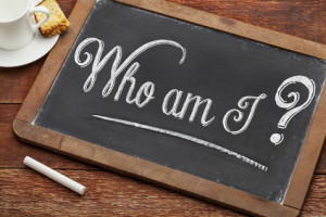 Chalkboard with wooden surround features the words 'Who am I?', with a piece of chalk on the table.