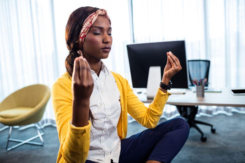 A black woman in her 20s sits cross-legged on the floor of her office meditating with her eyes shut.
