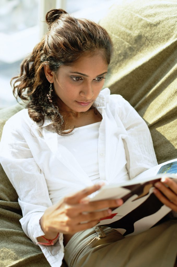 Woman in her 30s relaxes on a couch reading a magazine.