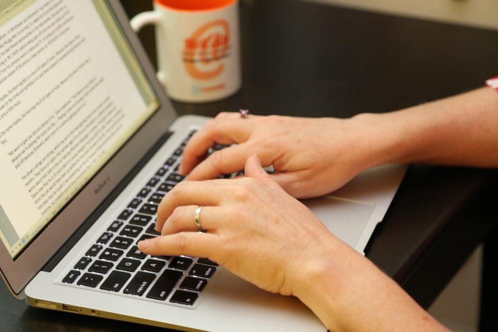 A coffee mug sits next to a laptop, where a woman types on a keyboard.