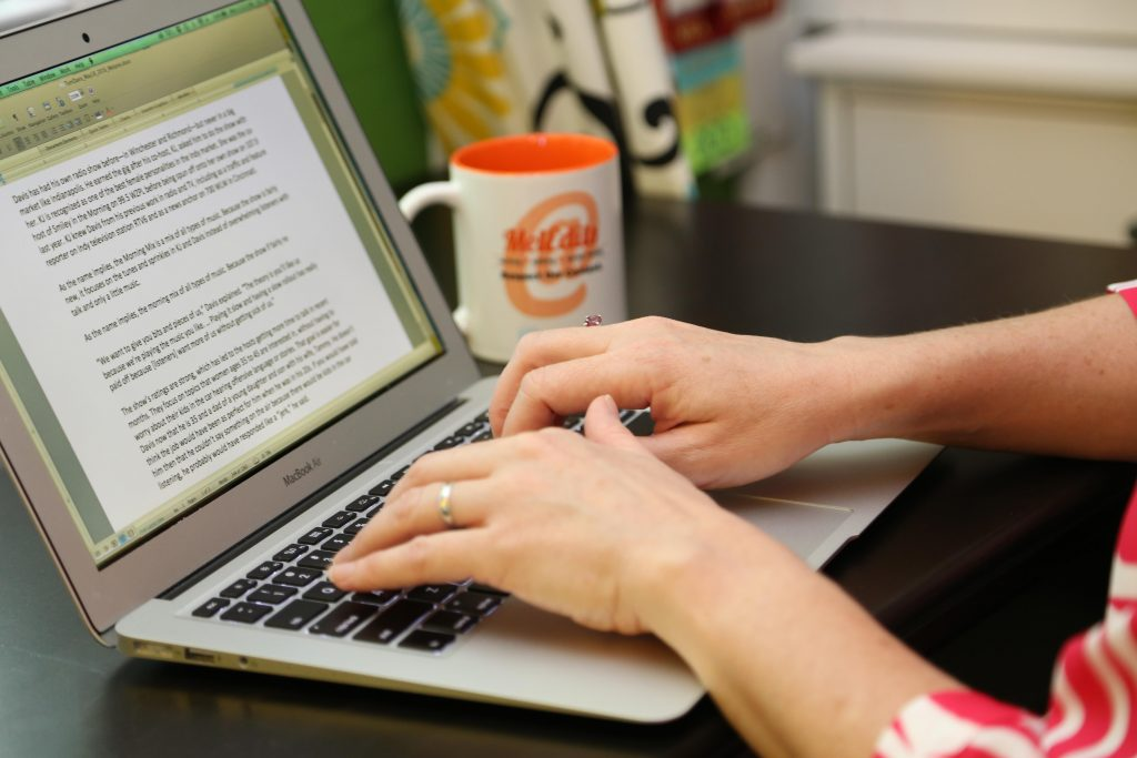 A woman sits at a desk typing on a laptop keyboard, with a coffee mug in the background.