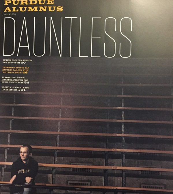 The cover of the spring issue of Purdue Alumnus magazine. It says Dauntless in big letters and shows a lone man in a hoodie sitting in empty bleachers.