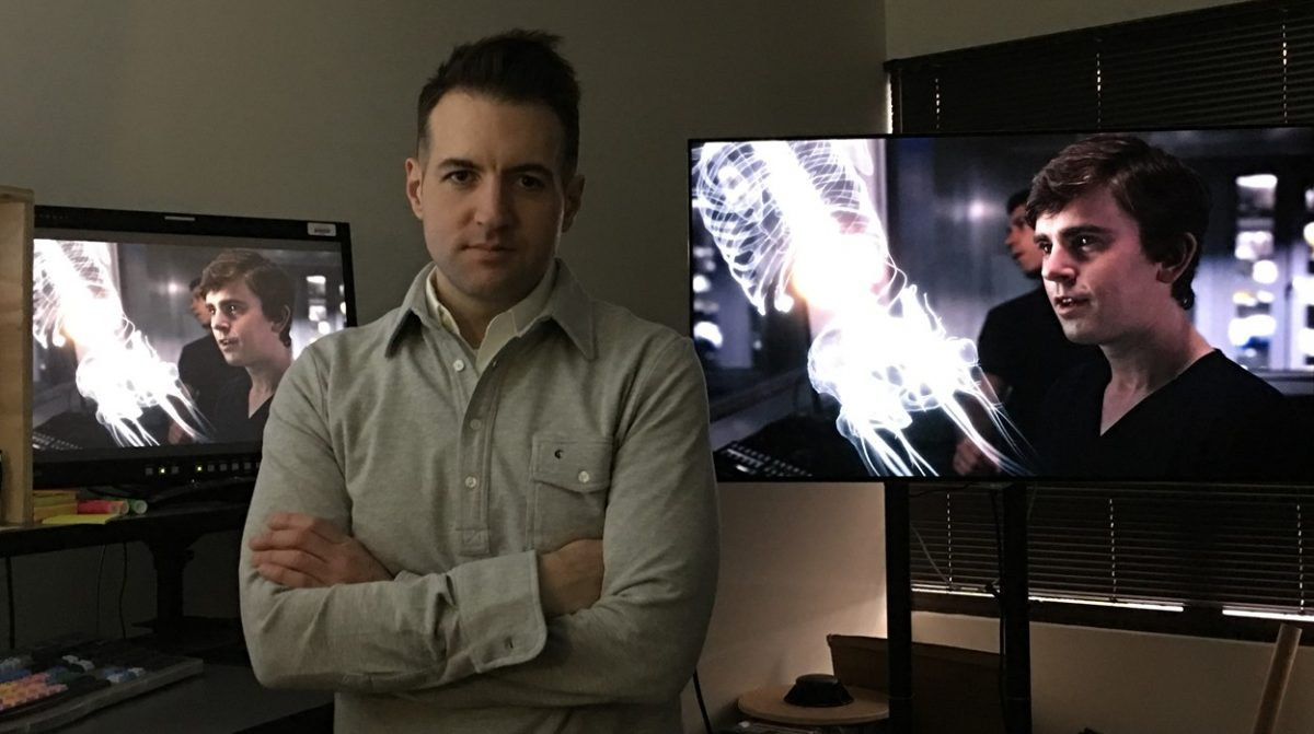 Aaron Rottinghaus stands facing camera with arms crossed with two big monitors on in the background showing a still scene from The Good Doctor TV show.