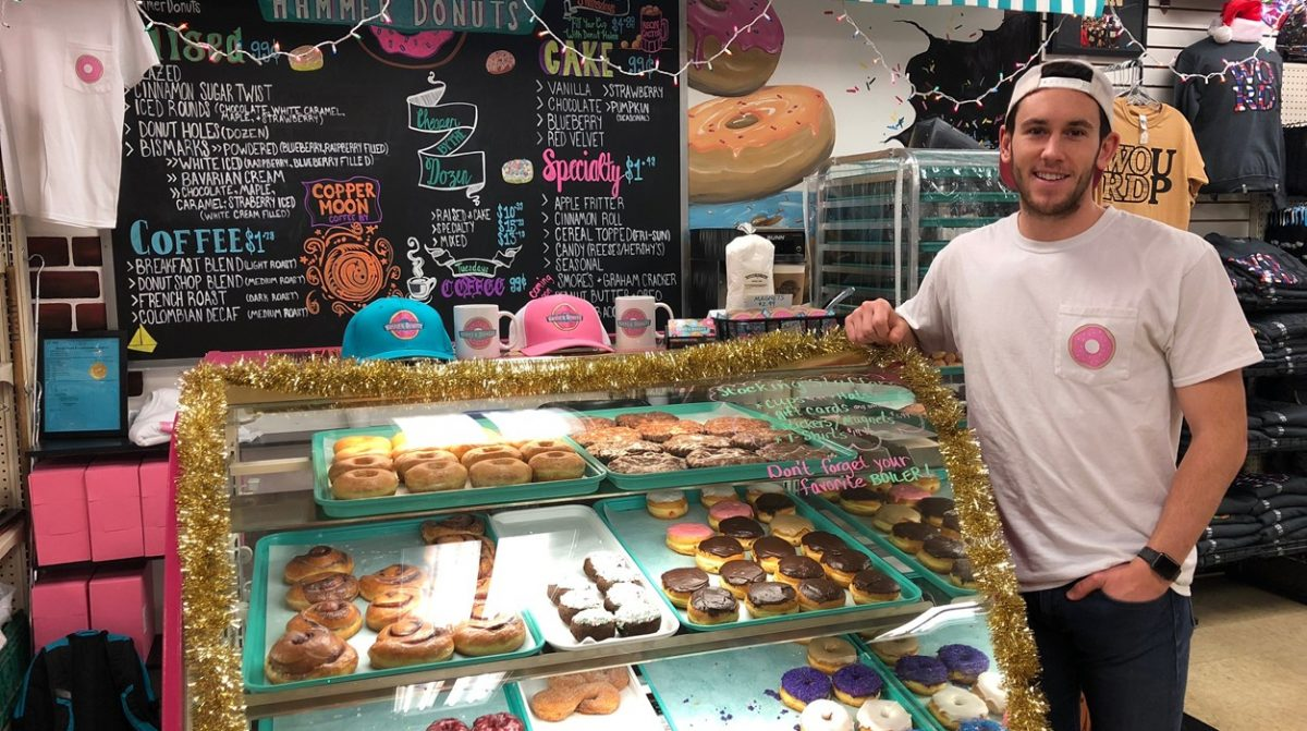 Tate Schienbein leans on glass case filled with donuts in small donut shop