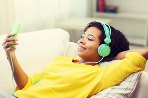 A woman in a yellow sweater lies back on a couch. She is wearing green headphones and holding her phone in her hand, listening to a podcast.